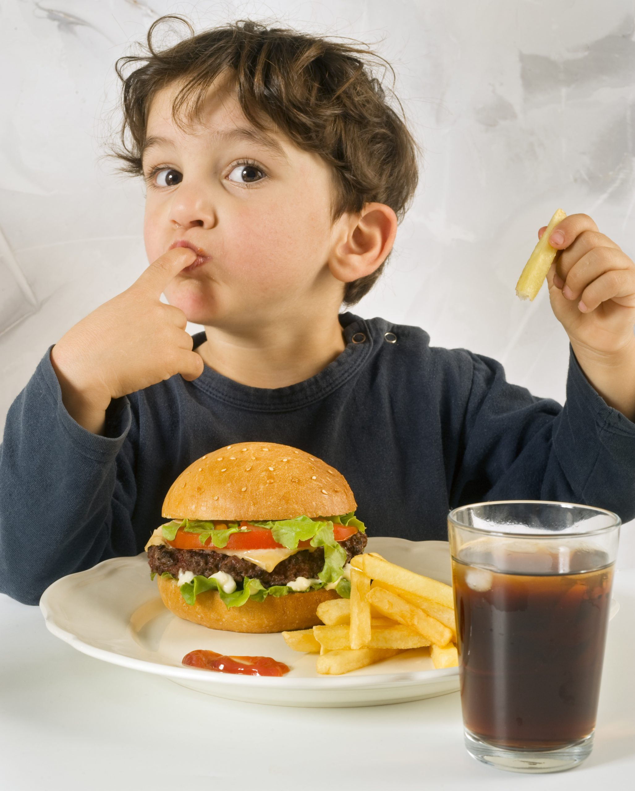 Young boy eating fast food